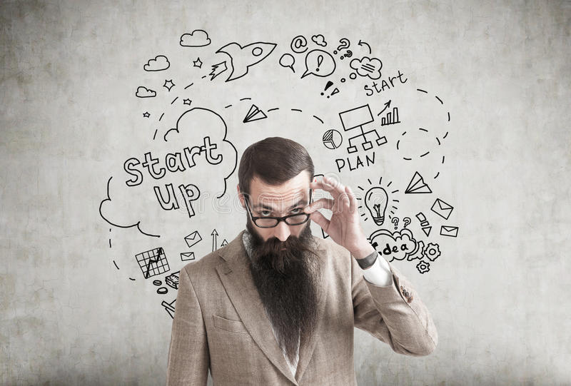 Skeptical man and start up icons on concrete royalty free stock image