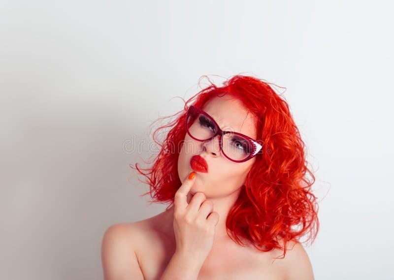 skeptical O retrato do close up confundiu a mulher cética com os vidros, olhando acima ao lado fotografia de stock