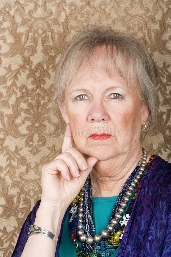 Skeptical Senior Woman. Portrait of skeptical senior woman in front of gold background royalty free stock photos