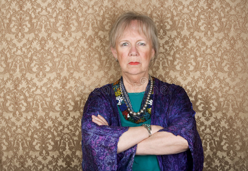 Skeptical Senior Woman. Portrait of skeptical senior woman in front of gold background stock photos