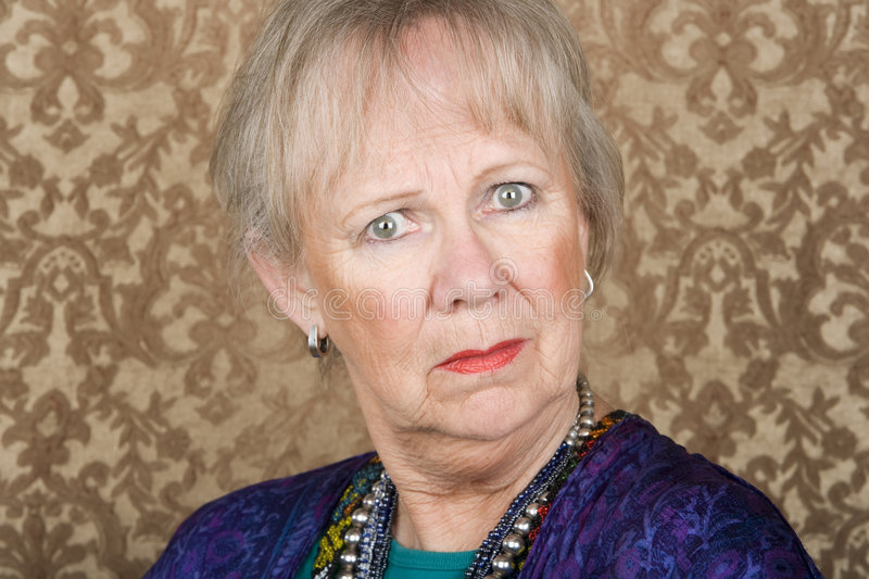Skeptical Senior Woman. Portrait of skeptical senior woman in front of gold background royalty free stock photo