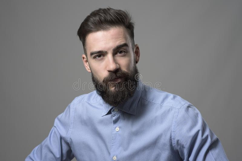 Skeptical suspicious young bearded stylish businessman looking at camera with one eyebrow raised. Against gray studio background stock images