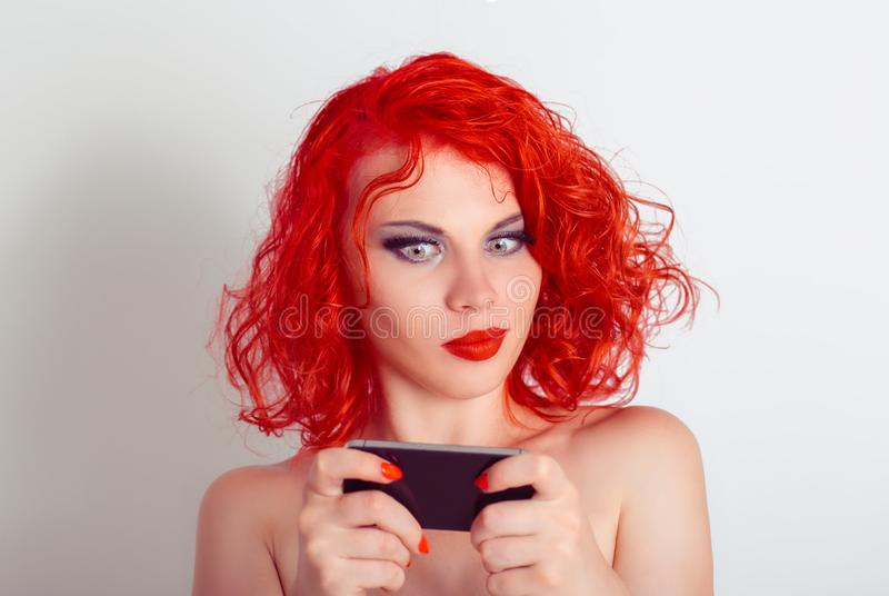 Skeptical woman looking at mobile phone texting receiving surprising message royalty free stock image