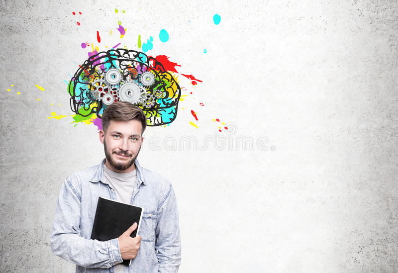 Skeptical young businessman and brain with cogs. Skeptical young businessman with wavy hair wearing glasses standing near a concrete wall with a colorful brain stock image