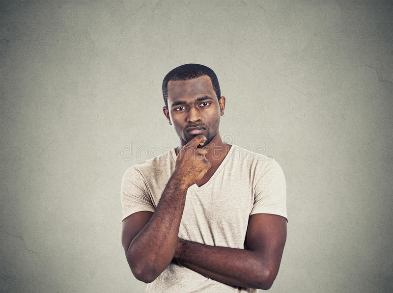 Skeptical young man. Looking at you camera isolated on gray wall background stock photo