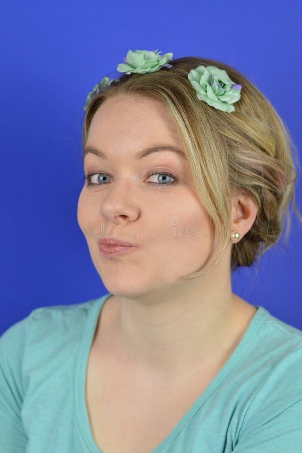 Skeptische junge blonde Frau mit Blumen auf einem Haar Circlet stockbilder