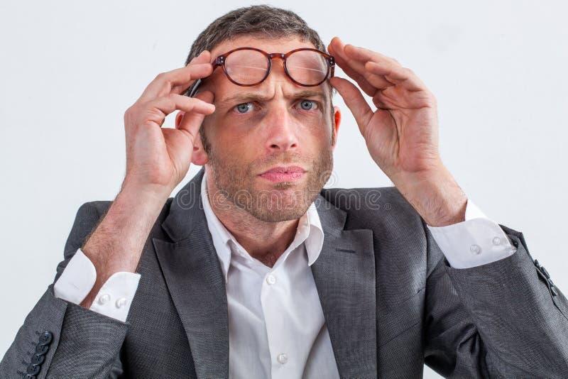 Skeptischer Geschäftsmann mit Brillen auf seiner Stirn für Misstrauen stockbilder