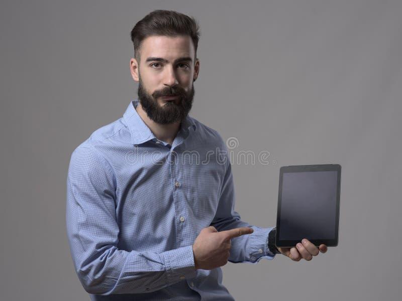 Skeptischer junger bärtiger Mann, der den Finger zeigt leeren Tablet-Computer-Schirm zeigt lizenzfreies stockbild