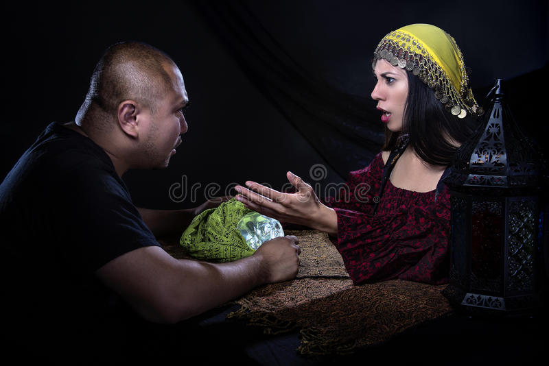 Skeptischer Mann mit Trickbetrüger Fortune Teller stockbild