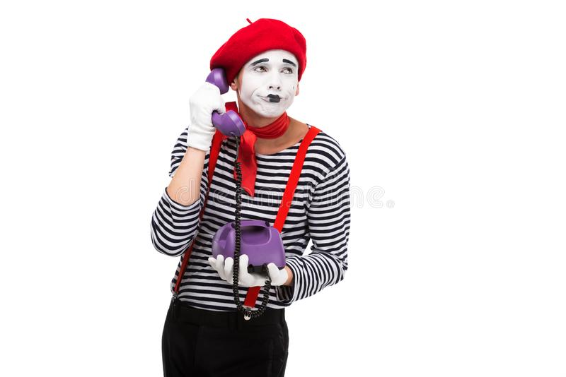 skeptischer Pantomime, der per ultraviolettes Retro- stationäres Telefon spricht lizenzfreies stockfoto