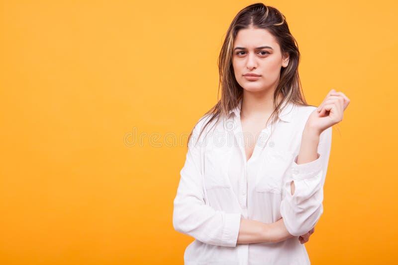 Skeptisk härlig ung flicka över gul bakgrund arkivbild