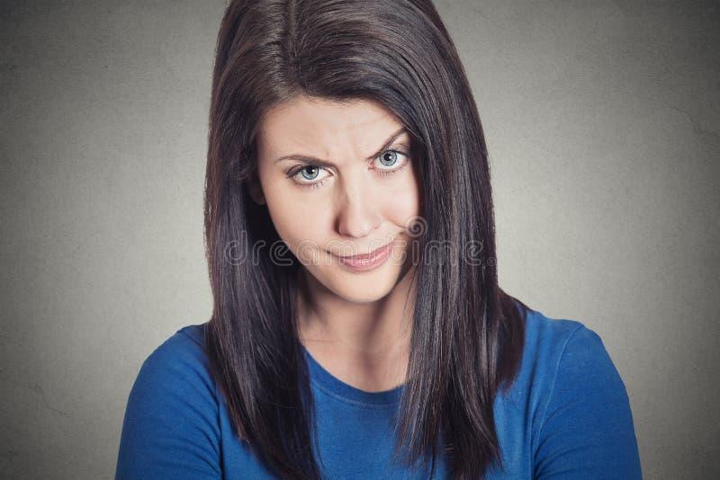 Skeptisk ung kvinna som ser misstänksam med avsmak på hennes framsida arkivfoton