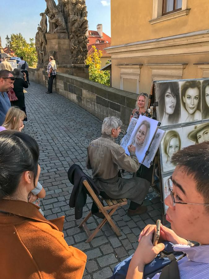 Sketch artist on the Charles Bridge, Prague, Czechoslovakia. September 2017: Sketch artist draws client on the Charles Bridge, Prague, Czechoslovakia stock photo