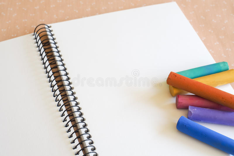 Sketch Pad with Soft Pastels. A white-papered spiral bound sketch pad with a selection of colored soft pastels, for drawing, coloring, artwork stock photography