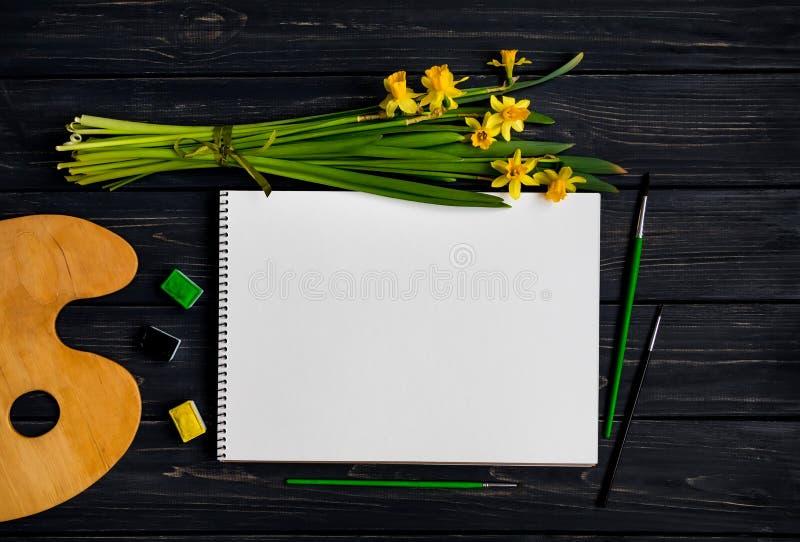 Sketchbook, acquerello e spazzole sulla tavola di legno nera con il mazzo dei narcisi Disposizione piana, vista superiore fotografie stock libere da diritti