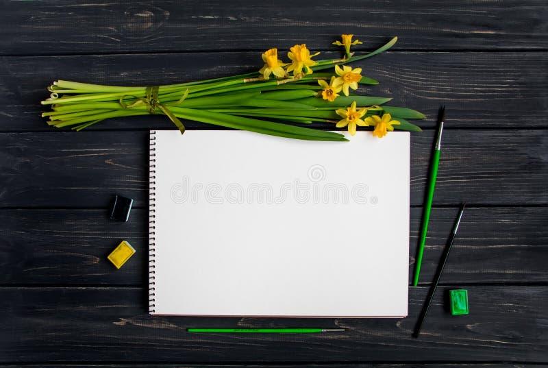 Sketchbook, acquerello e spazzole sulla tavola di legno nera con il mazzo dei narcisi Disposizione piana, vista superiore immagini stock