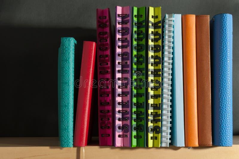 Sketchbook on the bookshelf. Notebook diary on black background on the bookshelf royalty free stock photos