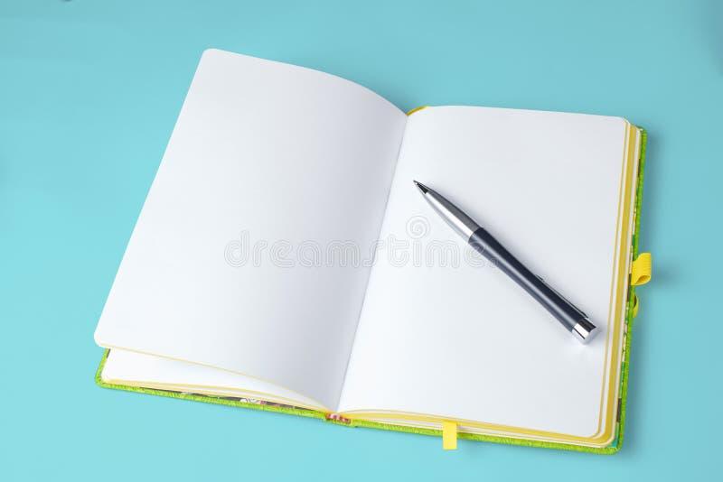Sketchbook med pennan på isolerad blå bakgrund arkivfoto
