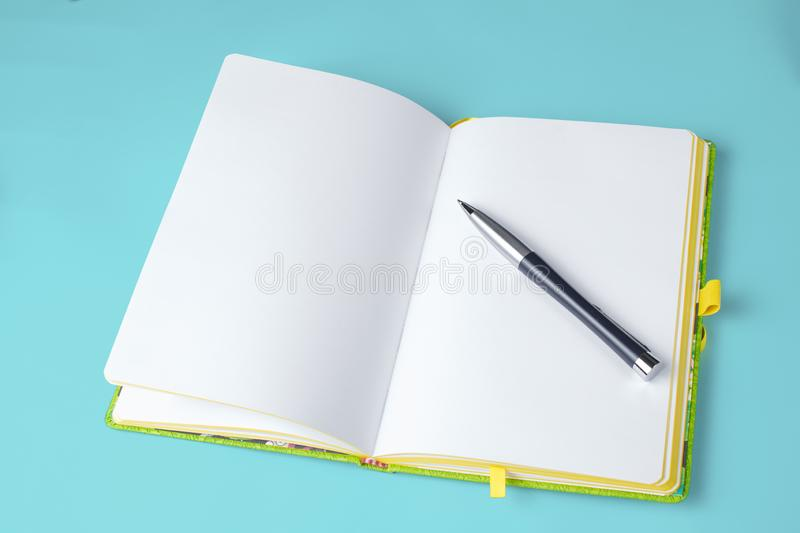 Sketchbook with pen on blue background isolated stock photo