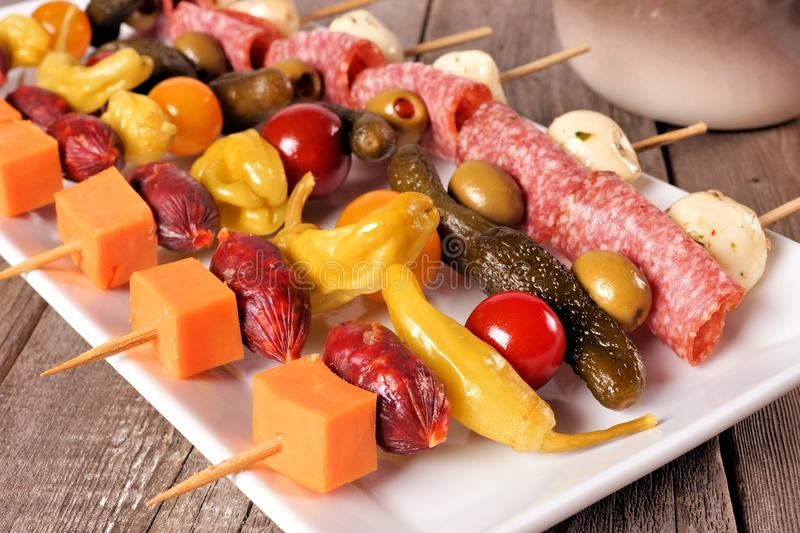 Skewer appetizers close up table scene. Skewer appetizers with cheese, meat and pickles close up table scene with a wooden background royalty free stock photos