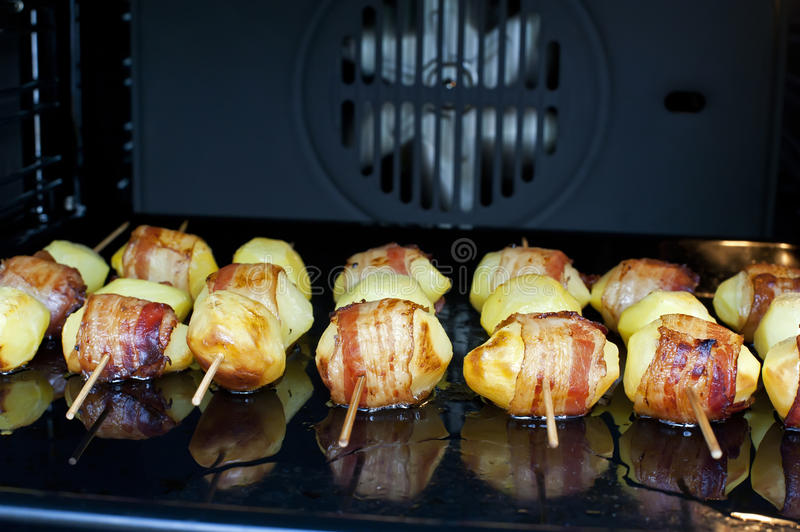 Skewer potatoes. The skewer potatoes with bacon in the roaster stock photography