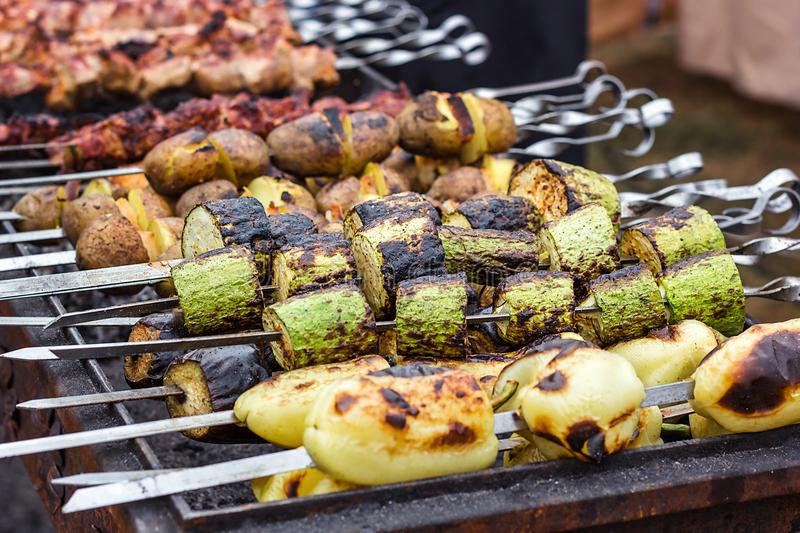 Skewered vegetables green zucchini courgettes cucumber peppers preparing barbecue grill charcoal Grilled roasted fried slices cove. Red beautiful crust royalty free stock images
