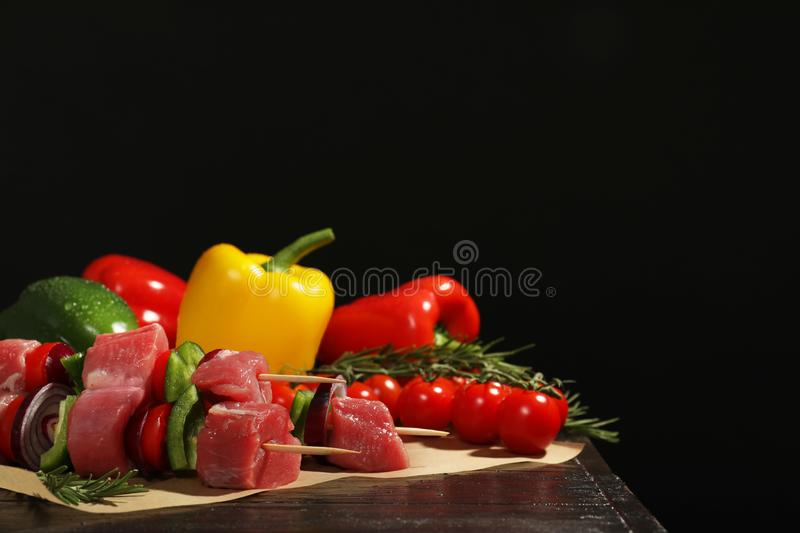 Skewers with fresh raw meat and vegetables on table against dark background. stock photography