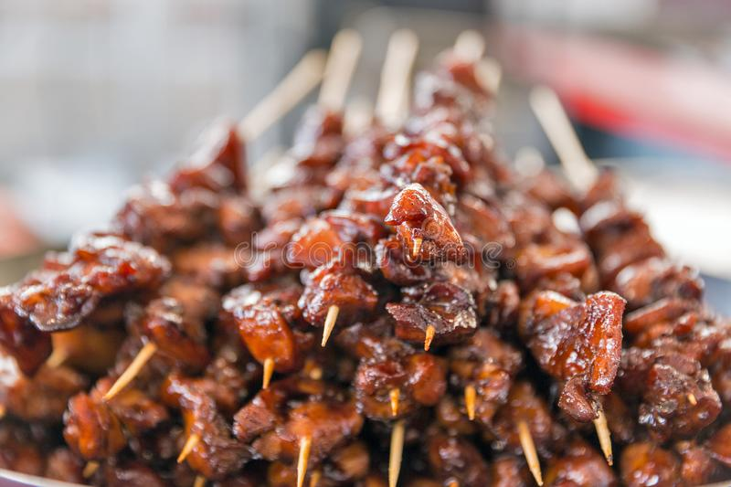 Skewers of meat pieces in sweet and sour sauce closeup stock photos