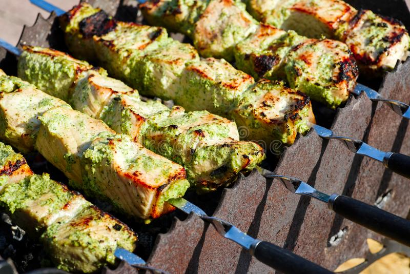 Skewers with pork meat under vegetable sauce stock photo