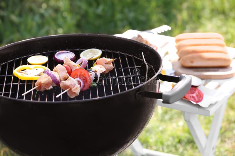 Skewers with raw meat and vegetables on barbecue grill outdoors royalty free stock photography