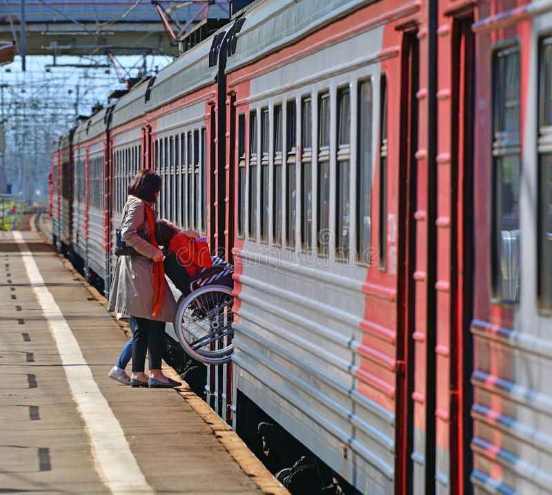 Skhodnya, Rússia - 9 de maio 2018 o homem na cadeira de rodas entra em um trem fotografia de stock royalty free