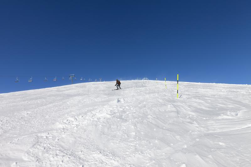 Skiër bergaf op sneeuwskihelling in zonnige de winterdag royalty-vrije stock afbeeldingen
