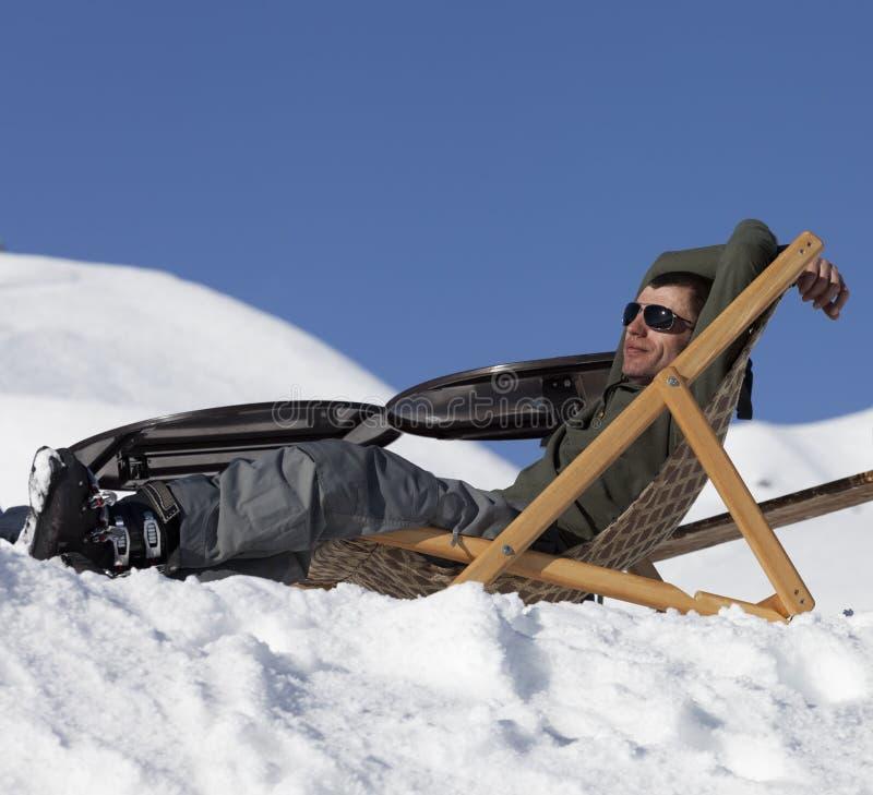 Skiër bij de winter sneeuwbergen die op zon-lanterfanter rusten royalty-vrije stock foto