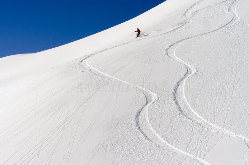 Skiër in de diepe poedersneeuw stock afbeeldingen