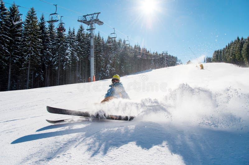 Skiër die op de helling op verse poedersneeuw bij de wintertoevlucht vallen royalty-vrije stock fotografie