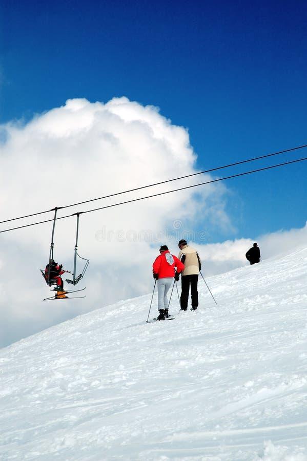 Skiër en berg stock afbeeldingen