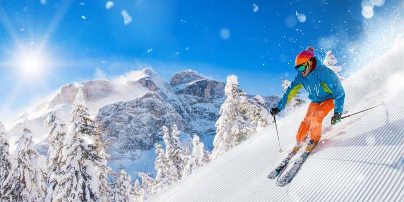 Skiër op piste die bergaf in mooi Alpien landschap lopen Blauwe hemel op achtergrond royalty-vrije stock foto