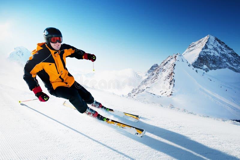 Skiër in voorbereide bergen, piste en zonnige dag stock foto