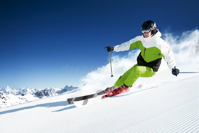 Skiër in voorbereide bergen, piste en zonnige dag royalty-vrije stock afbeelding