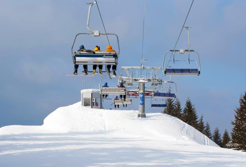 Skiërs die in stoeltjeslift tot bovenkant van berg aankomen stock afbeeldingen