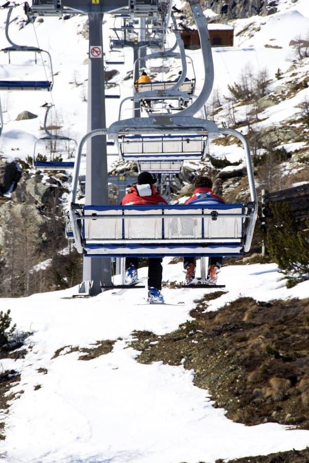 Skiërs op stoeltjeslift stock foto