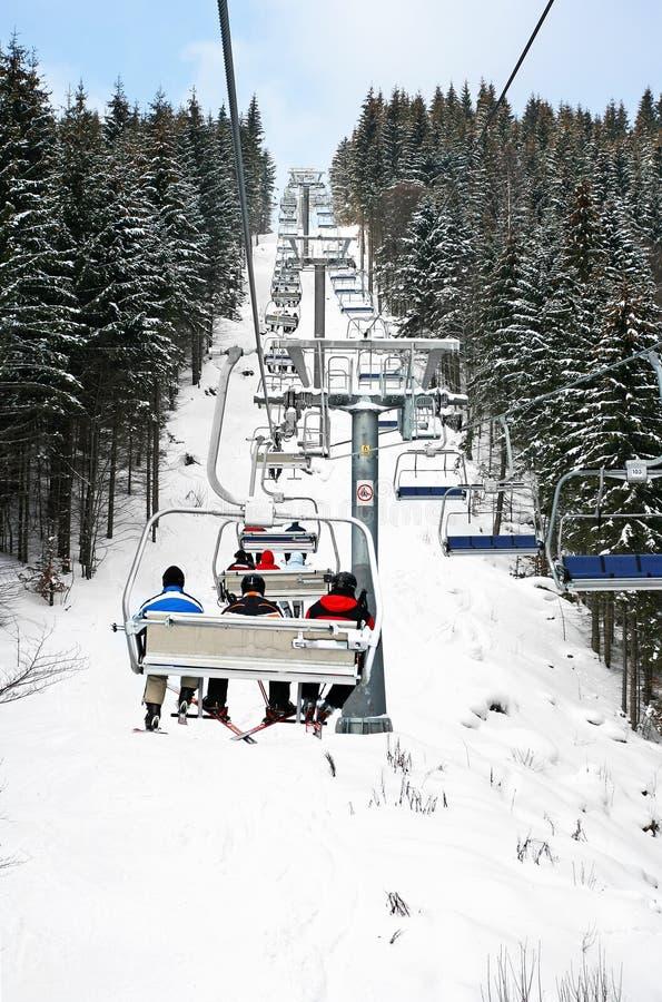 Skiërs in stoeltjeslift stock foto's