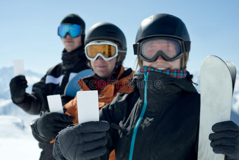 Ski admission fee ticket group of friends. Winter sport friends showing ski lift pass smiling. Concept to illustrate ski admission fee stock photos