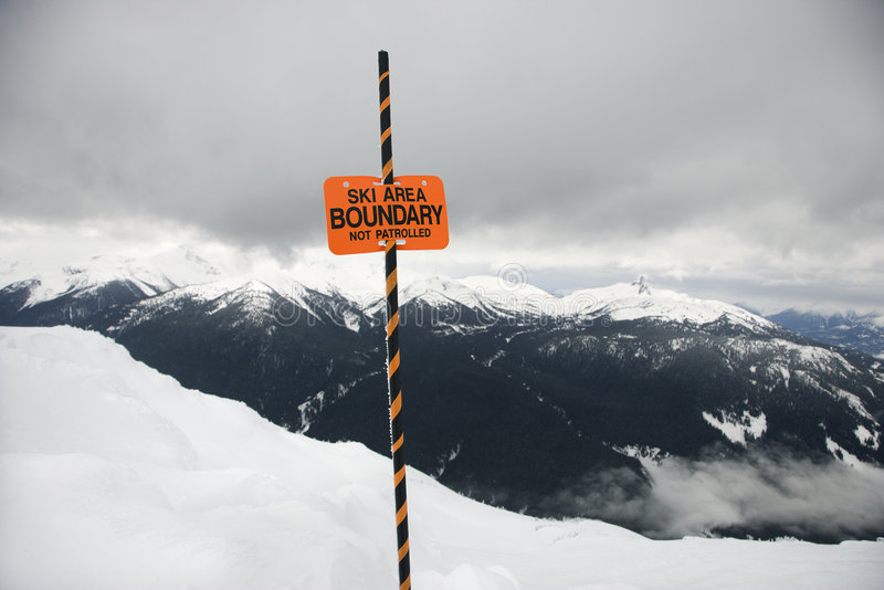 Ski area trail boundary sign. Ski area trail boundary sign with mountain landscape in background stock images