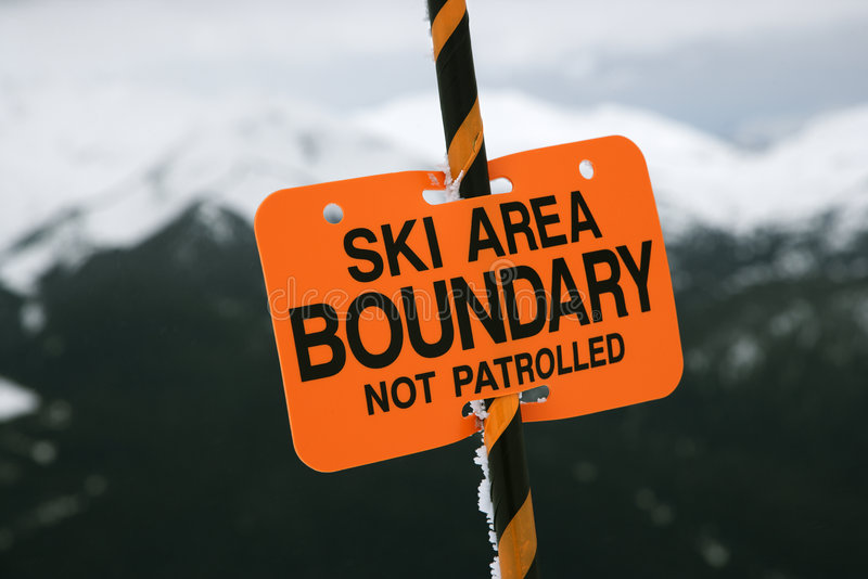 Ski area trail boundary sign. Ski area trail boundary sign with mountains in background royalty free stock images