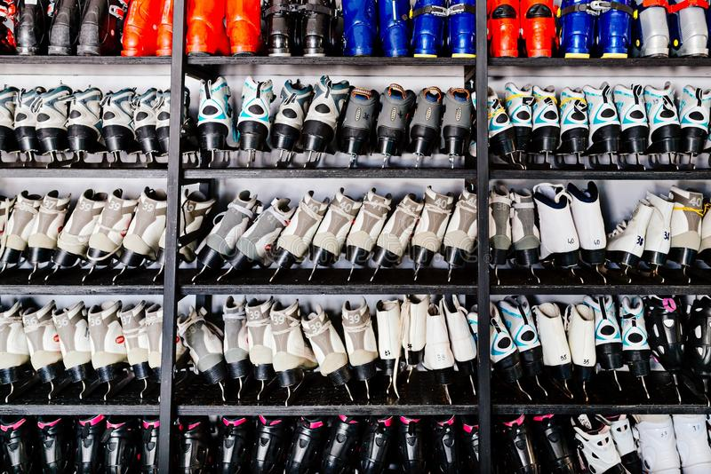 Ski boots and ice skates on shelf. In winter ski rent or shop stock photography
