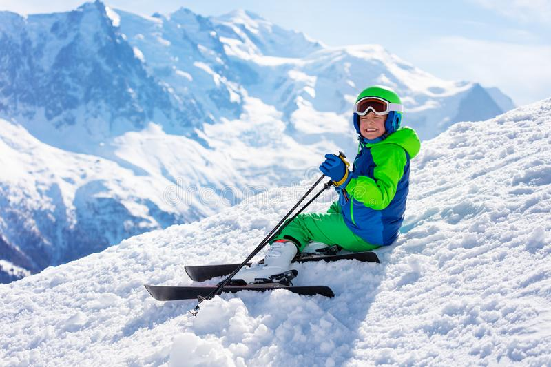 Ski boy sit on snow with mountain peak background. Close nice portrait of a little boy sit in snow on the alpine mountain trail slope ski path wear helmet and stock image