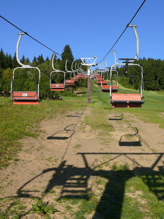 Ski chair lift. Empty ski chair lift in summer royalty free stock image
