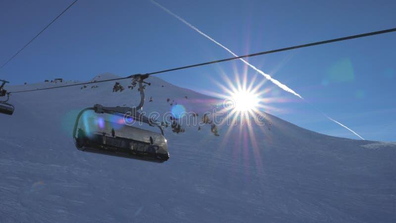 Ski Chair Lift In The bergThe Sun sken och solnedgång arkivbild