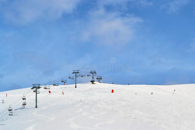 Ski chair lift  in France, with blue sky and few clouds - copy space above.  stock image